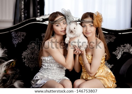 Two beautiful stylish woman with a rabbit