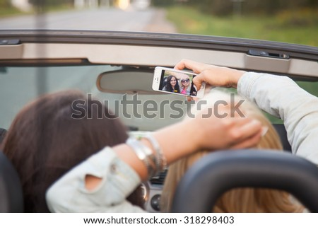 Two beautiful traveller girls taking selfie portrait with smartphone camera in car, sitting on passenger back seat of convertible, smiling, posing, having fun together, rear view