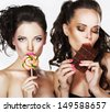 Two Beautiful Woman with Sweet - Lollipop and Chocolate Bar. Pleasure - stock photo