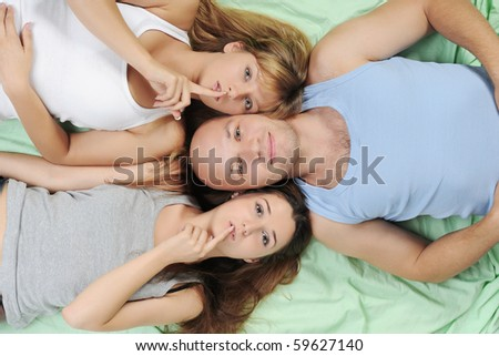 Two beautiful women and man lying on the bed