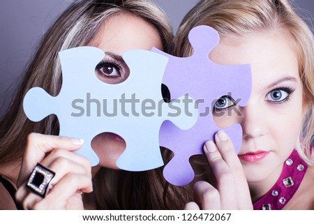 Two Beautiful women looking through game pieces at camera