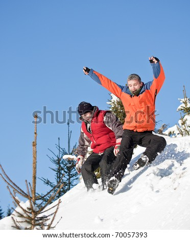 Two best friends sliding on the snow