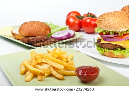 two big cheeseburgers and french fries with tomatoes and ingredients for another burger
