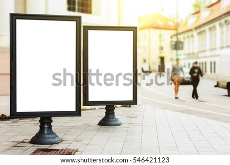 Two blank advertising billboards on the city street with pedestrians and sun glow