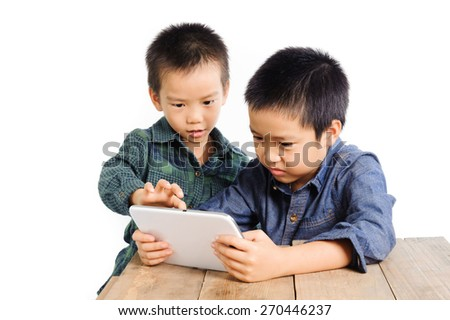 Two Boy sharing tablet device on wood table look happy on white background