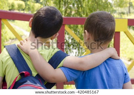 Two boys, friends, or brothers, holding around the shoulders, back view.
