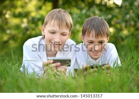 Two boys play a game on the phone outdoors