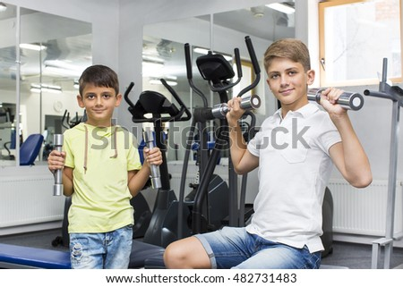 two boys play sports in the gym