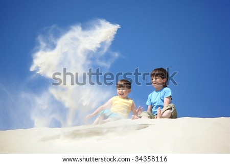 two boys sit on sand and scatter it