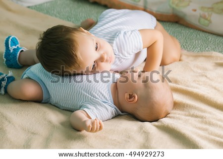 Two brothers cute babies blond boys children in rompers lie together on beige bed cover