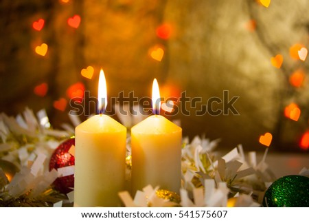 Two burning candles in a Christmas ornament with blurred background, bokeh