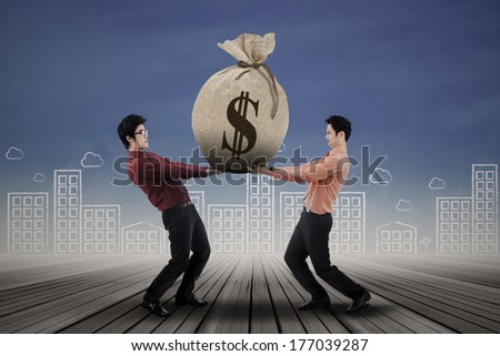 Two business people carrying a money bag with US dollar sign