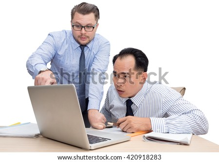 Two business people in bright shirts sitting at desk working in team together, discussing the problem, point finger on laptop, clipboard with papers, document, isolated on white