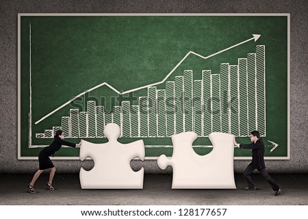 Two business people joining missing puzzle together on profit bar chart background