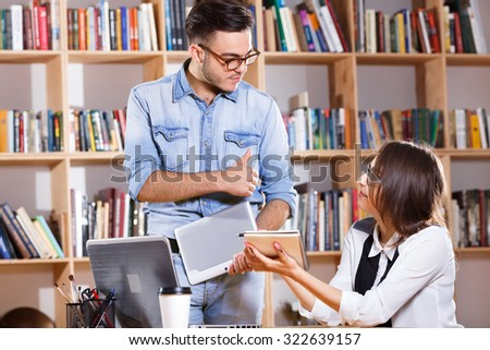 Two business people, wearing in casual clothes and glasses, are holding digital tablet and notebook and looking to each other, on the bookshelves background, in office, waist up