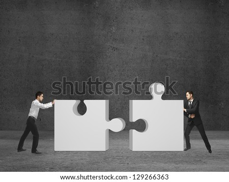 two businessman puts puzzle on room