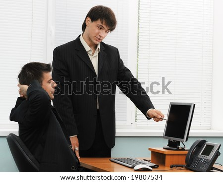 Two businessmen having a discussion at the computer
