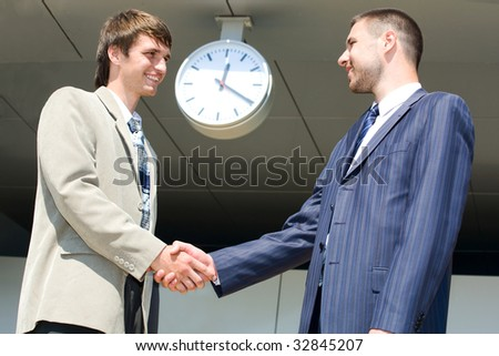 Two businessmen shaking hands under large clock