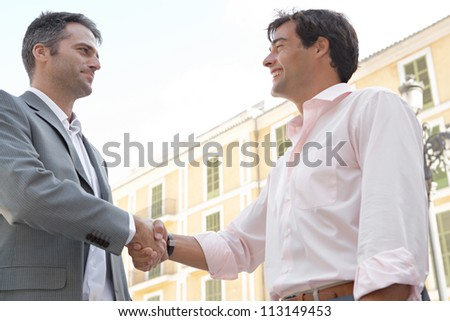 Two businessmen shaking hands while standing in front of a classic European building, outdoors.