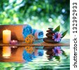 two candles and towels black stones and purple daisy on water - stock photo