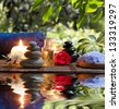 two candles and towels black-white stones and almond blossom on water - stock photo