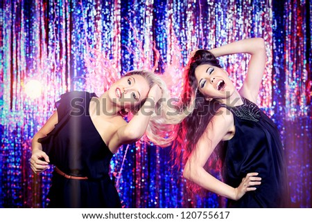 Two cheerful girls dancing at a party.