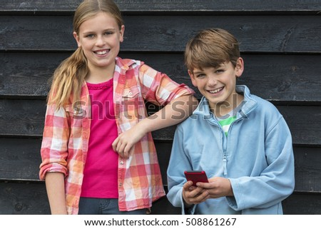 Two children boy and girl smiling and using cell phone