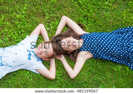 Two children lying on grass, their hands behind head