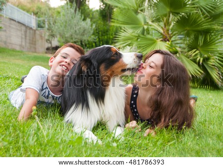 Two children lying on grass with a dog that is licking girl's face