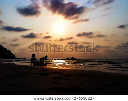 two children on the beach with sunset