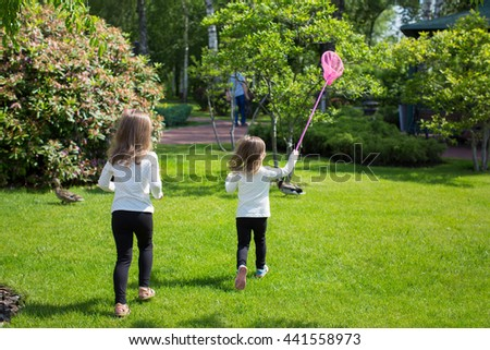 two children running with a scoop-net outside in the park