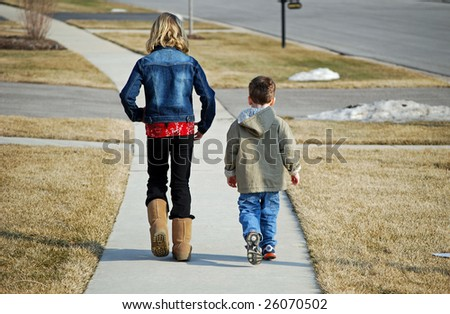 two children take a walk on one of the first warm days of early spring