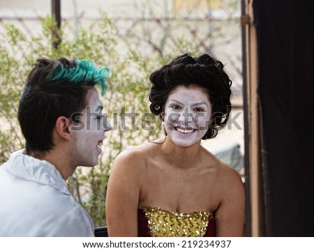 Two cirque performers in makeup laughing backstage