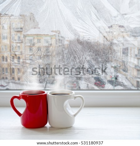 Two coffee cups on a window sill. The view from the window on city streets