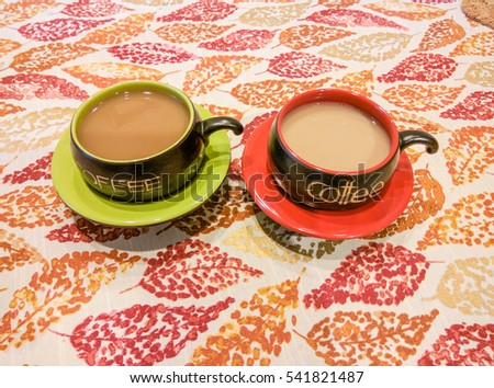 Two Coffee Cups The Table With Fall Themed Tablecloth.