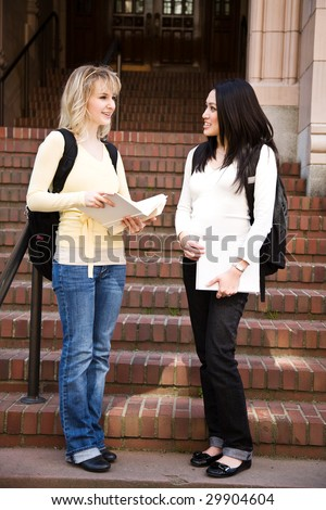 Two college students meeting and talking on campus