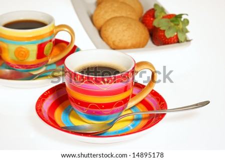 Two colorful cups of coffee, some biscuits and strawberries isolated on white