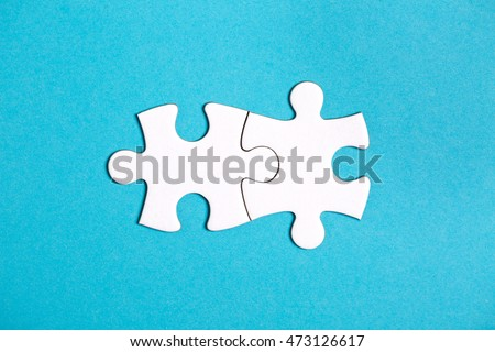 Two connected jigsaw puzzle pieces on blue background. The concept of finding the right solutions in teamwork.