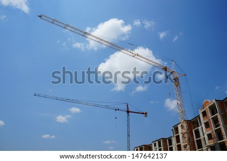 Two construction cranes next to new buildings