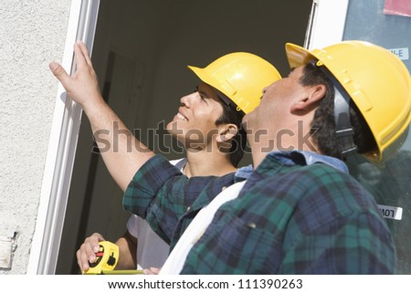 Two construction workers with measure tape standing near window