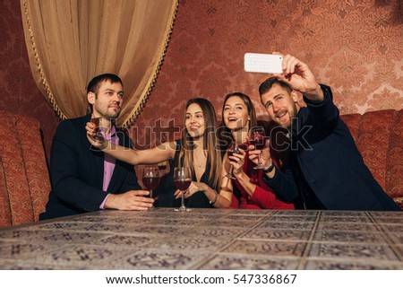 two couples at the party take a selfie with glasses