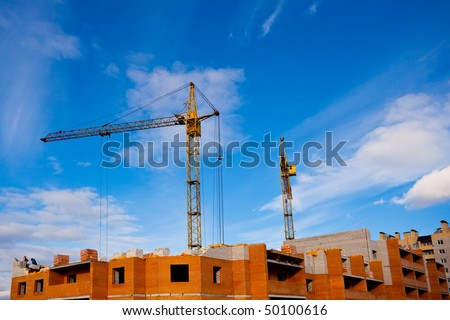 Two cranes and unfinished house