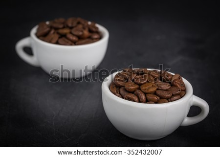 Two cup full of coffee beans on the black wooden table.