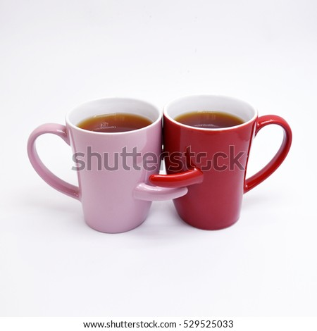 Two cups of coffee and stand together to be heart shape on white background with smile face on cup.