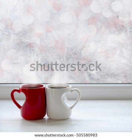 Two cups of coffee on the window sill. In the background frosty pattern on window as a Christmas background