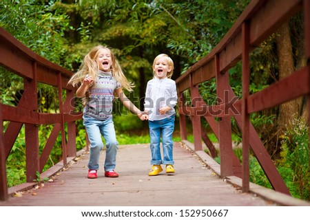 Two cute european blond sisters on scenic bridge together having fun with colorful summer forest on background