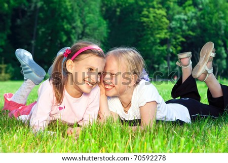 Two cute girls laughing on the green grass