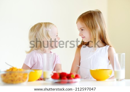 Two cute little sisters eating cereal with strawberries and drinking milk in white kitchen