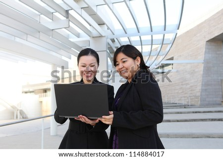 Two diverse business woman at office building with laptop computer