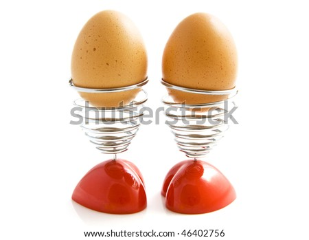 Two eggs in two heart egg cups isolated over white